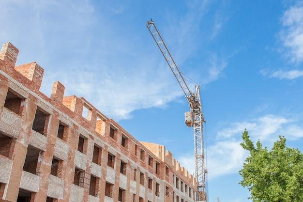 Bouwplaats van een nieuw hoog flatgebouw met torenkranen tegen blauwe hemel. woonwijk ontwikkeling.