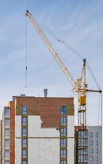 Bouwplaats van een nieuw woongebouw en torenkraan tegen een achtergrond van blauwe hemel.