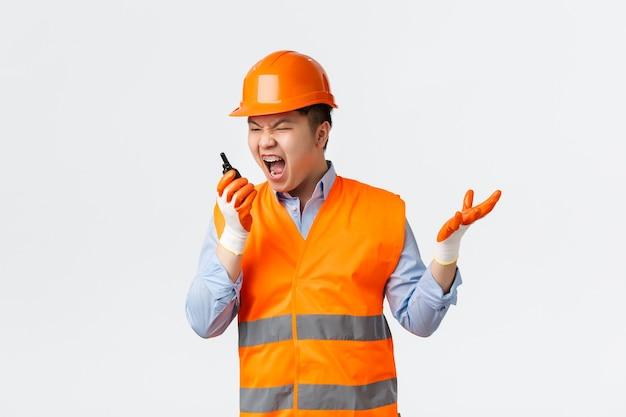 Bouwsector en industrieel arbeidersconcept boos en pissig aziatische hoofdingenieur die de wereld uitscheldt ...