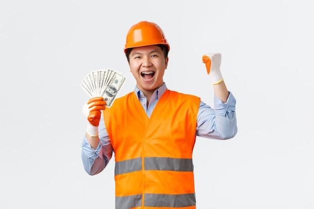 Bouwsector en industriële arbeidersconcept gelukkige zegevierende aziatische bouwmanager architect...