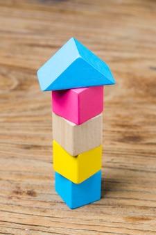 Bouwstenen op houten achtergrond, kleurrijke houten bouwstenen