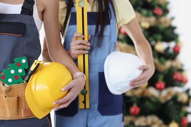 Bouwteam met hulpmiddelen op achtergrond van de bouw van de nieuwe jaarboom en kerstmisconcept