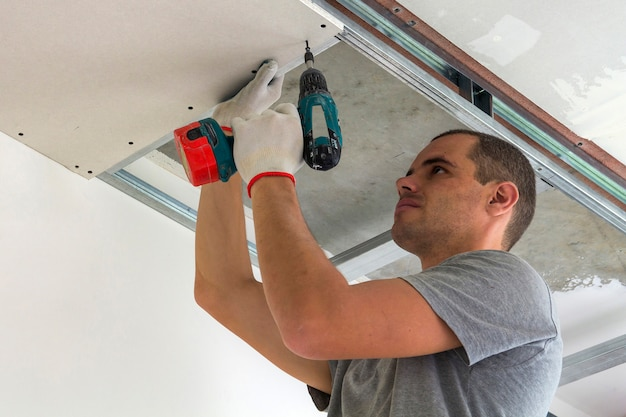 Bouwvakker assembleert een verlaagd plafond met gipsplaten en het bevestigen van de gipsplaten aan het plafond metalen frame met schroevendraaier.