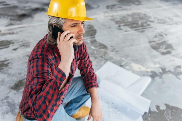 Bouwvakker die blauwdrukken controleert en op de telefoon spreekt