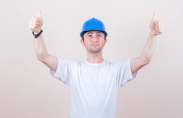 Bouwvakker die dubbele duimen toont in t-shirt, helm en er zelfverzekerd uitziet