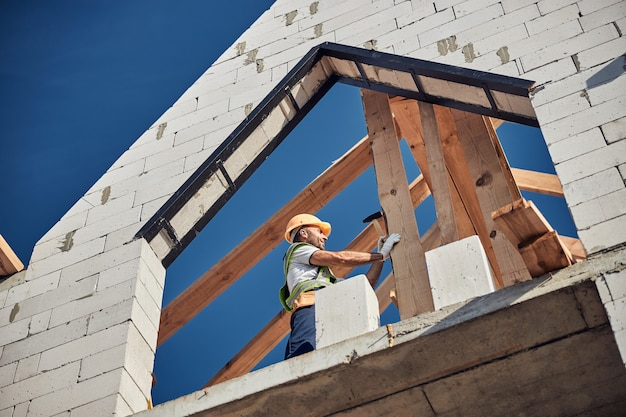 Bouwvakker die een oranje veiligheidshelm draagt en een spijker slaat met een hamer tijdens het bouwen van een huis