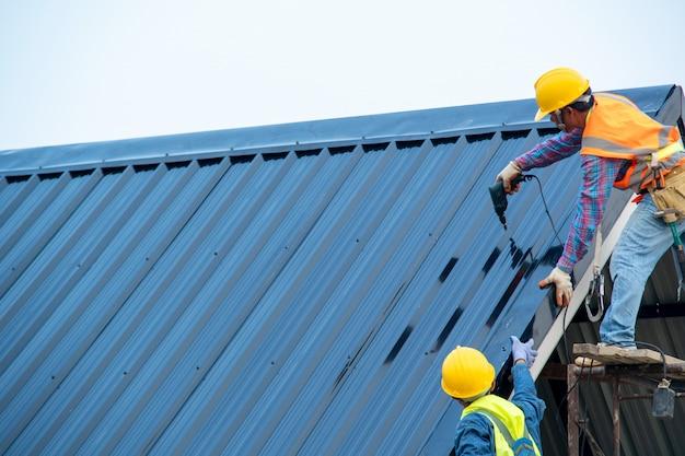 Bouwvakker die een veiligheidsharnas draagt met behulp van een secundair veiligheidsapparaat dat wordt aangesloten op een statisch touw van 15 mm met behulp van een valbeugel op het nieuwe dak.