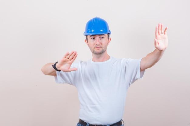 Bouwvakker die handen houdt om zichzelf te verdedigen in t-shirt, spijkerbroek, helm en resoluut kijkt