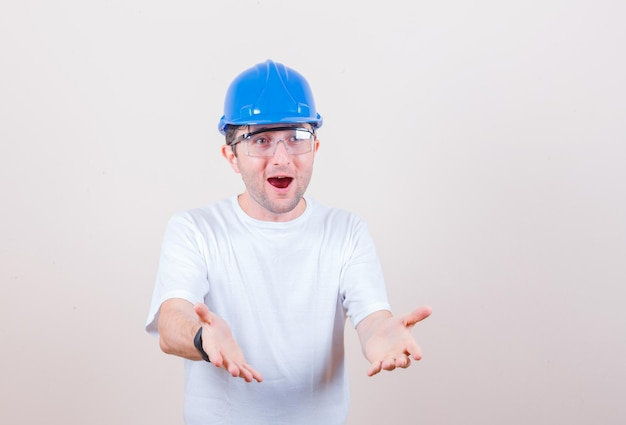 Bouwvakker die handen op vragende manier uitrekt in t-shirt, helm en verbaasd kijkt