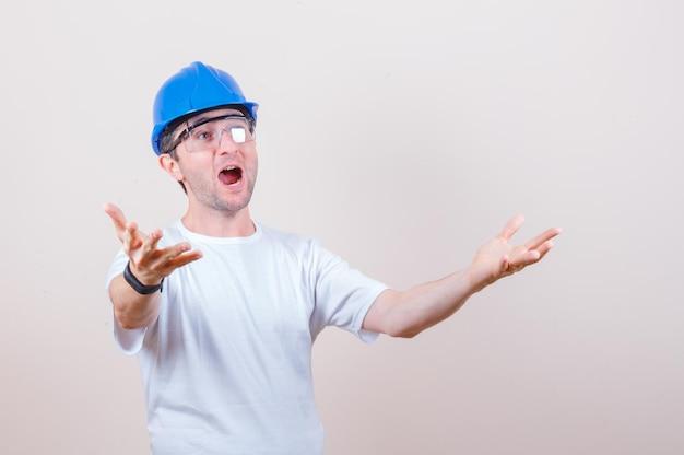 Bouwvakker die handen uitrekt in t-shirt, helm en verbaasd kijkt