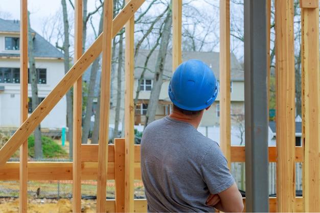 Bouwvakker die houtkader nieuw huis bouwt