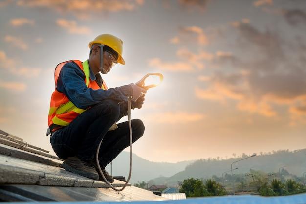 Bouwvakker die veiligheidsgordelriem dragen tijdens het werken op hoge plaats en concrete daktegel bovenop het nieuwe dak installeren, concept woningbouw in aanbouw.