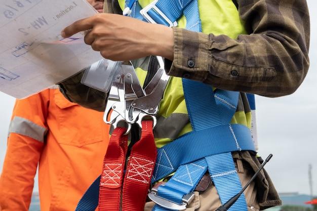 Bouwvakker die veiligheidsharnas draagt bij bouwwerf