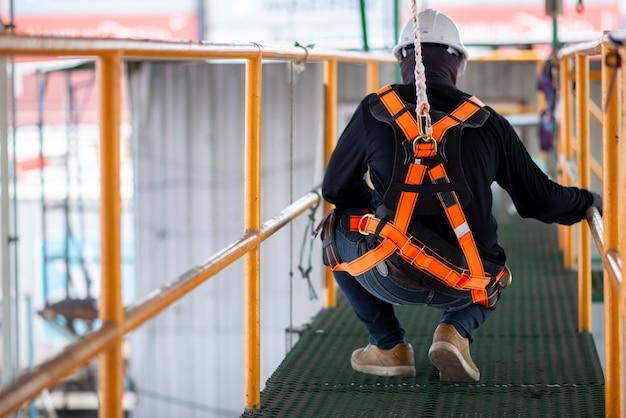 Bouwvakker die veiligheidsharnas en veiligheidslijn draagt die aan bouw werkt