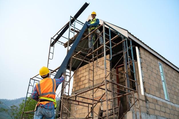 Bouwvakker die veiligheidsharnas en veiligheidslijn draagt die aan steigers bij nieuw huis in aanbouw werkt.