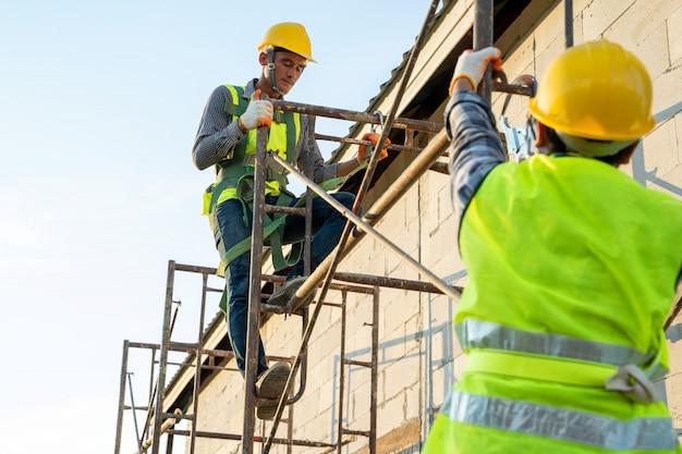 Bouwvakker die veiligheidsharnasgordel draagt tijdens het werken op hoge plaats, concept van woningbouw in aanbouw.