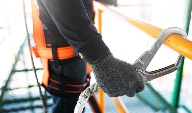 Bouwvakker die veiligheidsuitrusting en veiligheidslijn draagt die bij de bouw werkt