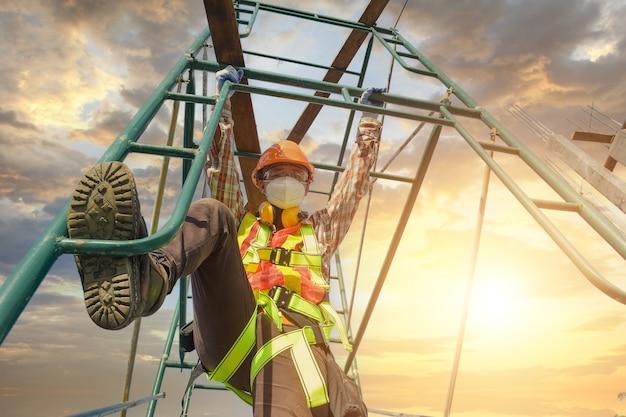 Bouwvakker die veiligheidswerk draagt bij hoog uniform op steigers op de bouwplaats tijdens zonsondergang, werken op hoogteapparatuur.