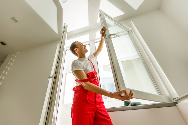 Bouwvakker die venster binnenshuis installeert