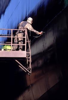 Bouwvakker die zich op opgeheven platform bevindt dat krachtige spuit met behulp van om muur te schilderen