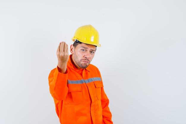 Bouwvakker doet italiaans gebaar, ontevreden over domme vraag in uniform, helm, vooraanzicht.