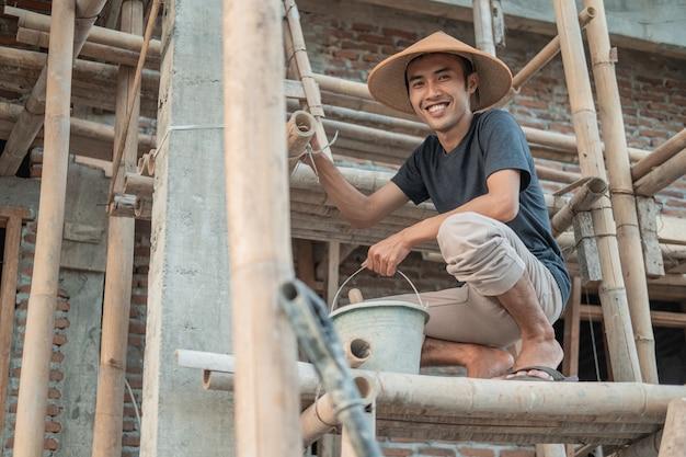 Bouwvakker glimlacht naar de camera terwijl hij op de bamboeplanken hurkt