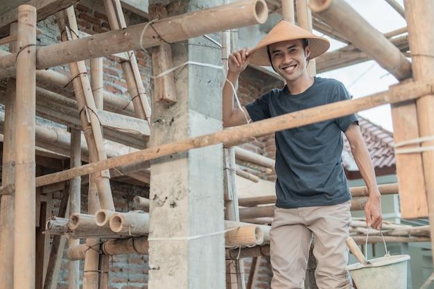 Bouwvakker glimlacht naar de camera terwijl hij tussen de bamboe en palen in het onafgemaakte huis staat