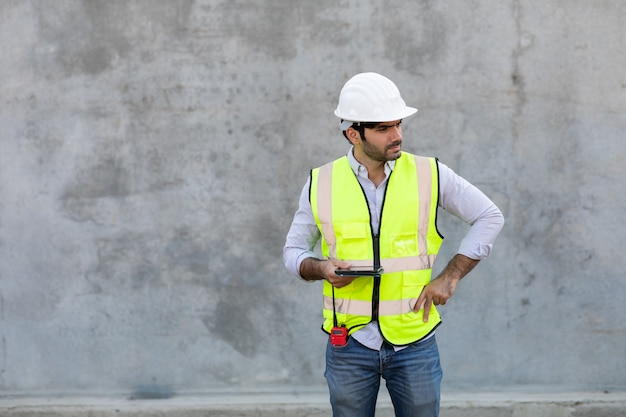 Bouwvakker houden en kijken op digitale tablet isoleren op grijze cement achtergrond. projectingenieur op bouwterrein.