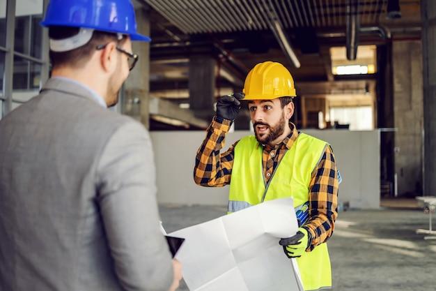 Bouwvakker houdt blauwdrukken en praat met zijn supervisor terwijl hij op de bouwplaats staat.
