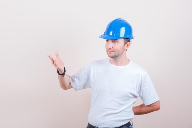 Bouwvakker houdt de hand op een vragende manier in t-shirt, spijkerbroek, helm en ziet er vrolijk uit