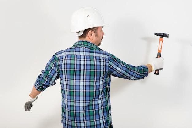 Bouwvakker in een beschermende helm slaat met een hamer tegen de witte muur