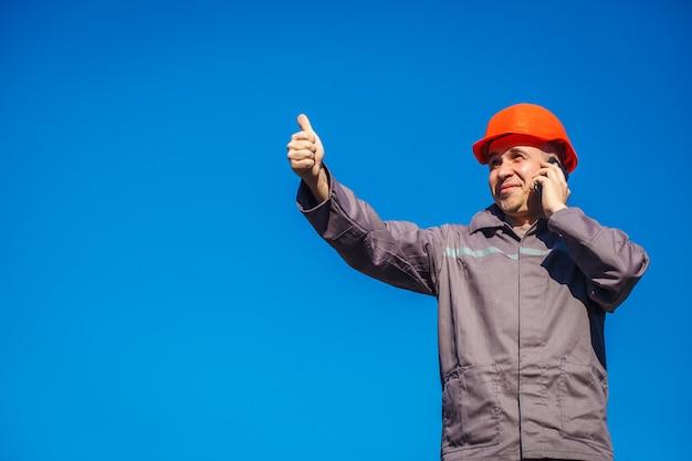 Bouwvakker in een helm tegen de blauwe hemel die op de telefoon spreekt.