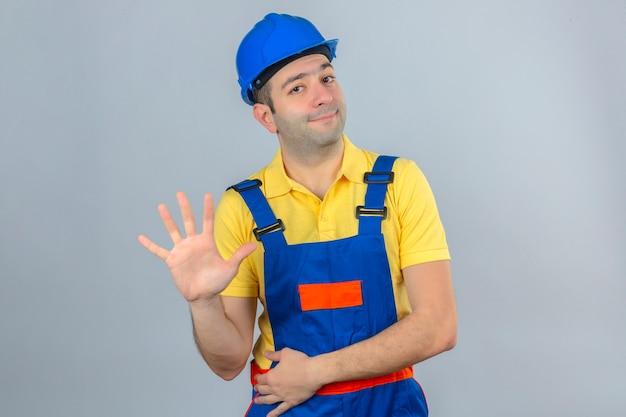 Bouwvakker in eenvormige en blauwe veiligheidshelm die en met vingers nummer vijf tonen tonen met glimlach op gezicht dat op wit wordt geïsoleerd