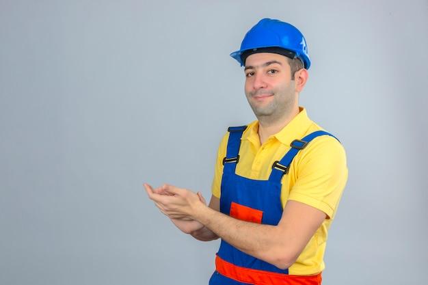 Bouwvakker in eenvormige en blauwe veiligheidshelm die met glimlach op gezicht toejuicht dat op wit wordt geïsoleerd