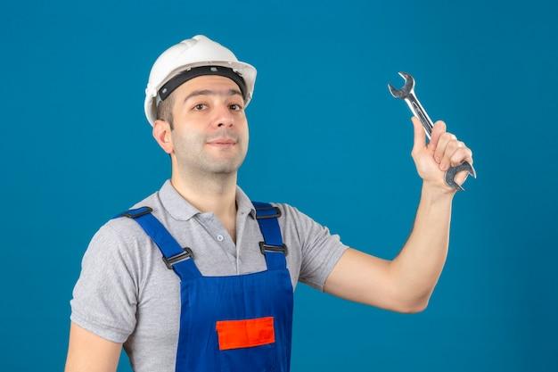 Bouwvakker in eenvormige en veiligheidshelm met moersleutel in het opheffen van hand op geïsoleerd blauw