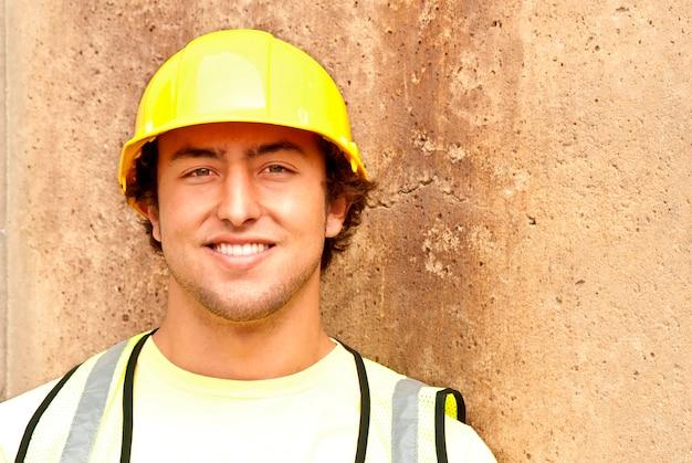 Bouwvakker in reflecterend vest en bouwvakker glimlachen