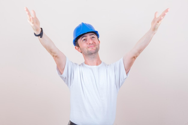 Bouwvakker in t-shirt, helm die armen opent voor knuffel en er vrolijk uitziet