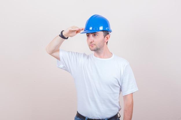 Bouwvakker in t-shirt, spijkerbroek, helm die een groetgebaar toont en er gefocust uitziet