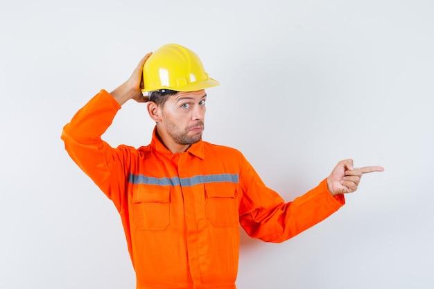 Bouwvakker in uniform, helm wijst naar de zijkant en kijkt peinzend, vooraanzicht.