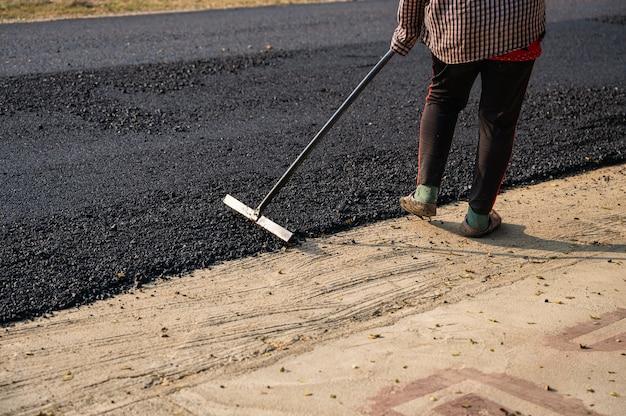 Bouwvakker met behulp van gereedschap spreidde de hete asfaltweg nauwkeurig uit op de beschadigde snelweg