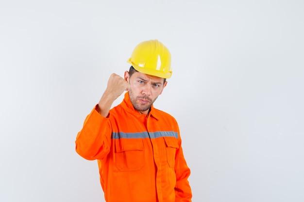 Bouwvakker met gebalde vuist in uniform, helm en op zoek naar vertrouwen, vooraanzicht.
