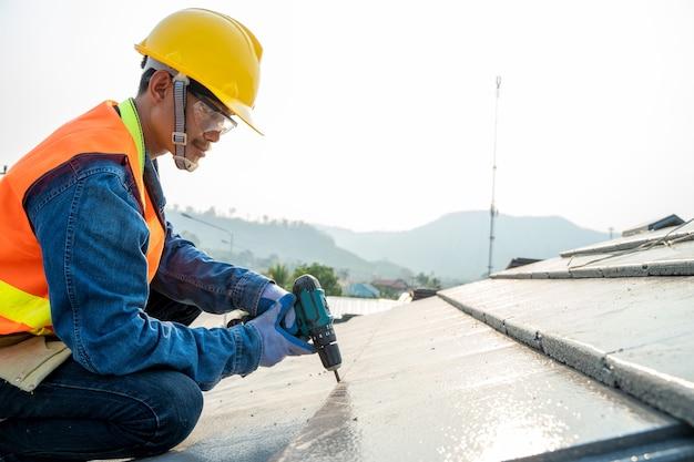 Bouwvakker met spijkerpistool nieuw dak installeren in het gebouw in aanbouw.