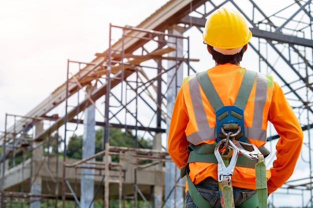 Bouwvakker met veiligheidsharnas en veiligheidslijn die op een hoge plaats werkt.praktijken op het gebied van veiligheid en gezondheid op het werk kunnen gevarenbeheersing en interventies gebruiken om gevaren op de werkplek te verminderen.