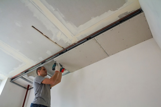 Bouwvakker monteer een verlaagd plafond met gipsplaat en bevestig de gipsplaat aan het metalen frame van het plafond met een schroevendraaier.