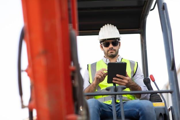 Bouwvakker rijden graafmachine of graafmachine op bouwplaats. jonge spaanse man met zware apparatuur