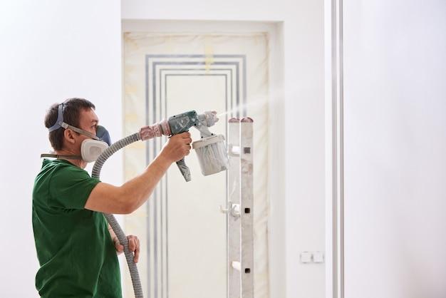 Bouwvakker schilderende muur met spuitpistool in witte kleur
