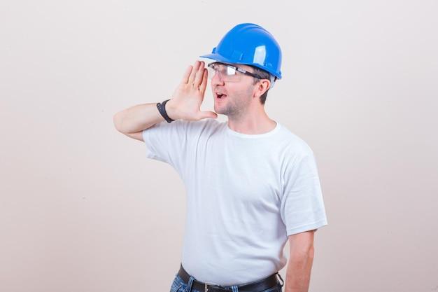 Bouwvakker schreeuwt naar iemand in t-shirt, spijkerbroek, helm