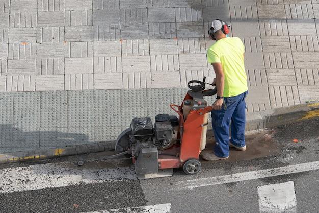 Bouwvakker snijden betonnen vloer met diamantzaagblad machine op een stoep