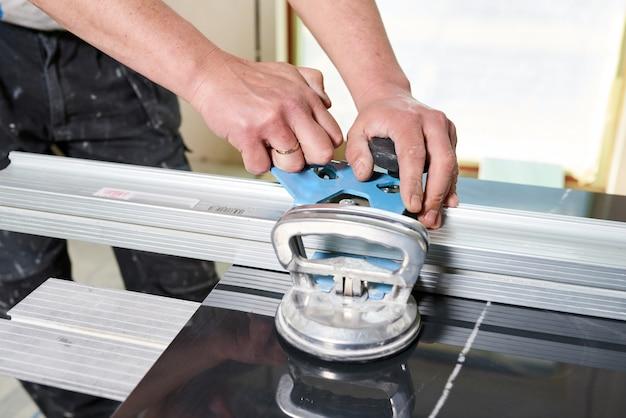 Bouwvakker snijden van keramische tegels met behulp van keramische snijder