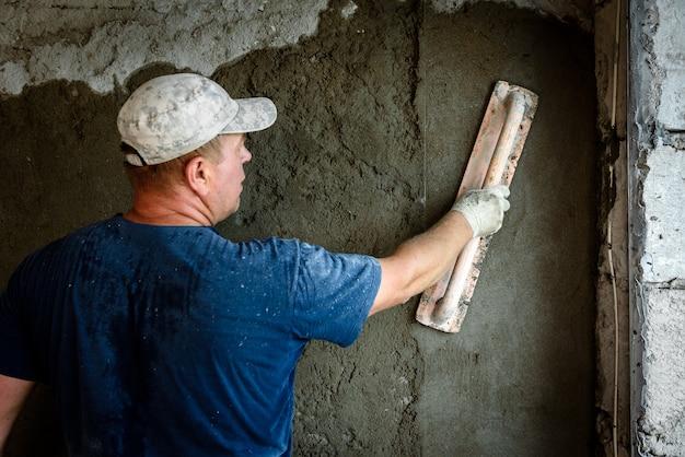 Bouwvakker stukadoors muur met leveller.